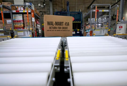 A box of merchandise is unloaded from a truck and sent along a conveyor belt at a Walmart Supercenter in Houston on Nov. 9, 2018.