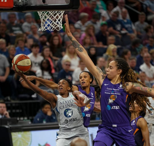 Minnesota Lynx guard Danielle Robinson (3) splits the defense of Phoenix Mercury forward DeWanna Bonner and center Brittney Griner, right, during the second quarter of a WNBA basketball game Thursday, June 6, 2019, in Minneapolis. Griner blocked the shot.