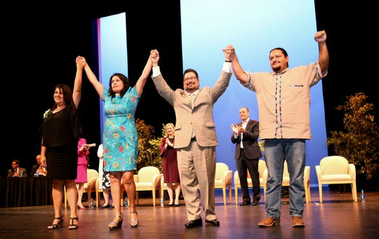 City of Phoenix councilmembers Betty Guardado, Laura Pastor, Michael Nowakowski and Carlos Garcia (right) step to the front of the stage and raise their hands after Guardado and Garcia took the oath of office during inauguration ceremony on June 6, 2019, at the Orpheum Theatre in Phoenix, Ariz.