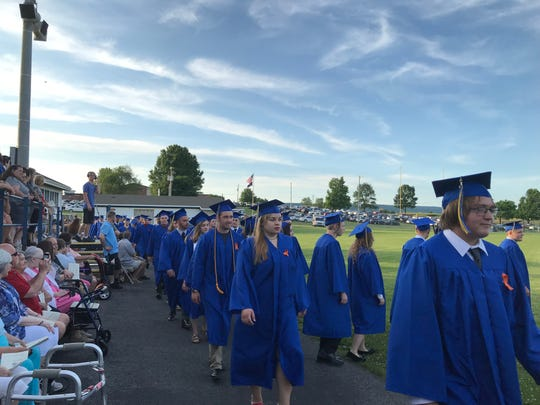 Students wearing orange ribbons on their robes file into Northern Lebanon High School's graduation Thursday night.