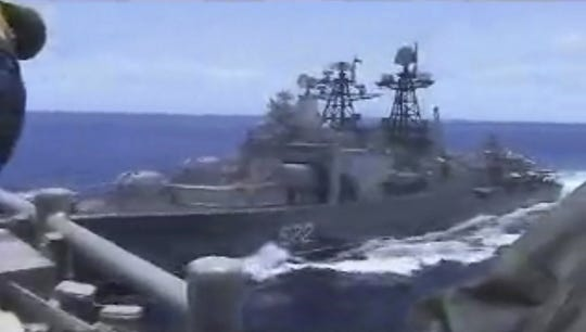 In this image from video provided by the U.S. Navy, a Russian destroyer, left, sails very close to the USS Chancellorsville, right, while operating in the Philippine Sea, Friday, June 7, 2019. The U.S. and Russian militaries accused each other of unsafe actions in the incident. (Photo by Petty Officer 1st Class Christopher J Krucke)