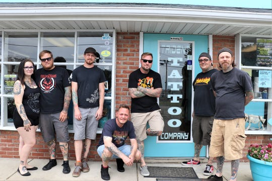 Employees of Trident Tattoo Company pose at the front of the store for a photo on Friday, June 7.