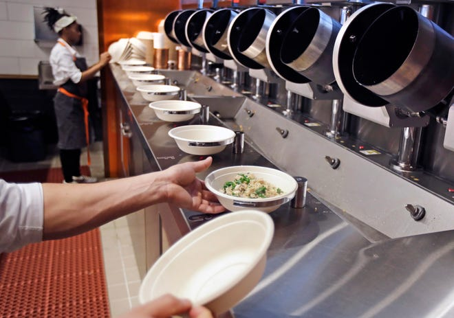 In this May 3, 2018, file photo a worker lifts a lunch bowl off the production line at Spyce, a restaurant which uses a robotic cooking process, in Boston.