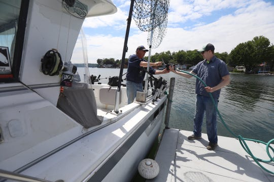 Lake Ontario levels continue to flood Sodus Point residents and businesses.  Although many businesses have to pump out water many are open for business.  Brian Noger, employee at Arney's Marina in Sodus Point, hands the gas pump to Jim Van Hooft, who was filling up his boat's tank getting it ready for a couple of charter fishing trips he has.