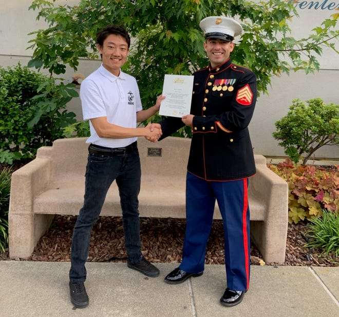 Shawn Xiong, left, poses with a U.S. Marines recruiter.