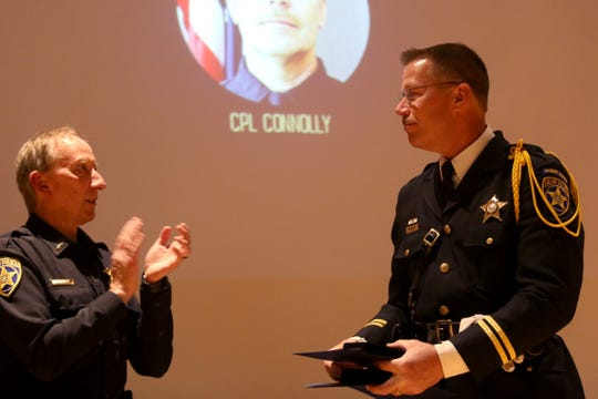 Cpl. Andrew Connolly, right, is recognized for both the Purple Heart and the Medal of Honor by Chief Jerry Moore during the Salem Police Department Awards and Promotions Ceremony in the Loucks Auditorium at the Salem Public Library on June 7, 2019.