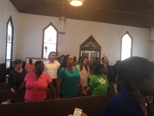 Attendees hold hands during a service held in Capeville, Virginia on Thursday, June 6, 2019 to respond to the fatal shooting of 12 people in a Virginia Beach municipal building on May 31.