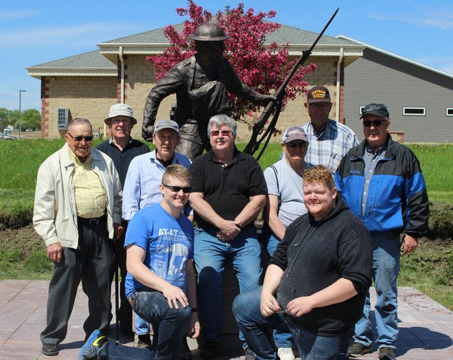 A new statue was placed at Veterans Memorial Park on May 26. Pictured (left-to-right):  Bill Huntimer, Doug Munk, Dan DeVaney, Steve Sittig, Bob Mergen, Tom Reecey, Larry Hovde.  Kneeling in front are members of the transport crew from Utah who brought the statue from Utah.