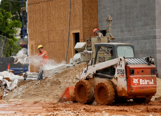 Crews mix concrete while working on the four-story, 98-room Tru By Hilton hotel at 525 E. Elm St. on Friday, June 7, 2019.