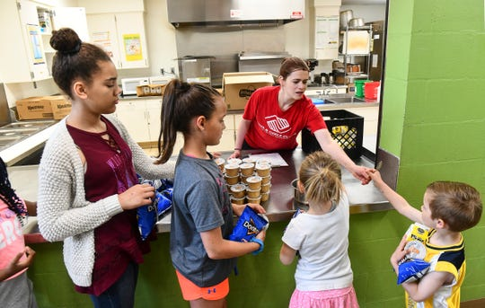 Chef Michelle Dalton hands out lunch items Wednesday, June 5, at the Eastside Boys & Girls Club in St. Cloud.