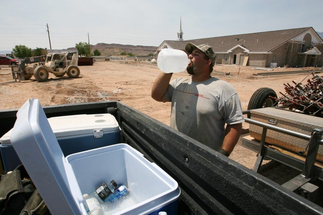 Tripple B Concrete employee Curt Kitteridge downs a drink of water after finishing a day of pouring concrete in this Spectrum file photo.