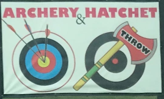 Sign advertising archery and hatchet throwing at the St. Lucie Golf Range.
