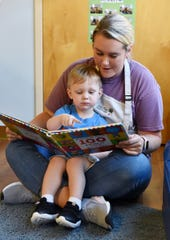 A child is helped reading a book at Park Place Children's Center.