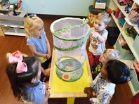 Children look at butterflies and larvae at Disciples Child Development Center.