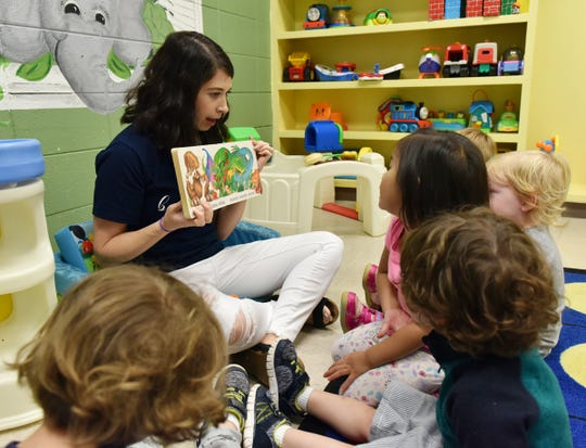 Children are read a book at St. James Day School.