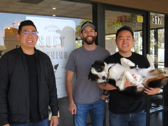 From left, David Ju, Marco Valdovinos and Steve Kim pose with Braxton, the Australian shepherd-border collie mix who is the inspiration for their Camarillo restaurant, Braxton's Kitchen. Its grand opening June 8-9 will serve as a fundraiser for the animal-rescue organization Paw Works.