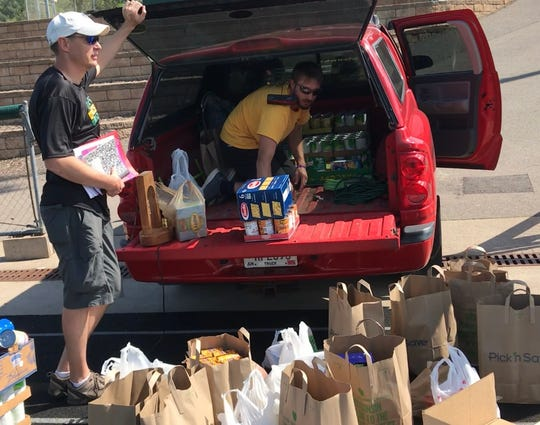 D.C. Everest High School teachers Mike Soehl and CJ Hansen load a pickup truck with the food donated during Seeley Steps.