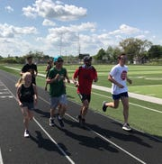A handful of runners accompany Brad Seeley, center in red shirt, as he nears the finish of his 50-mile run.