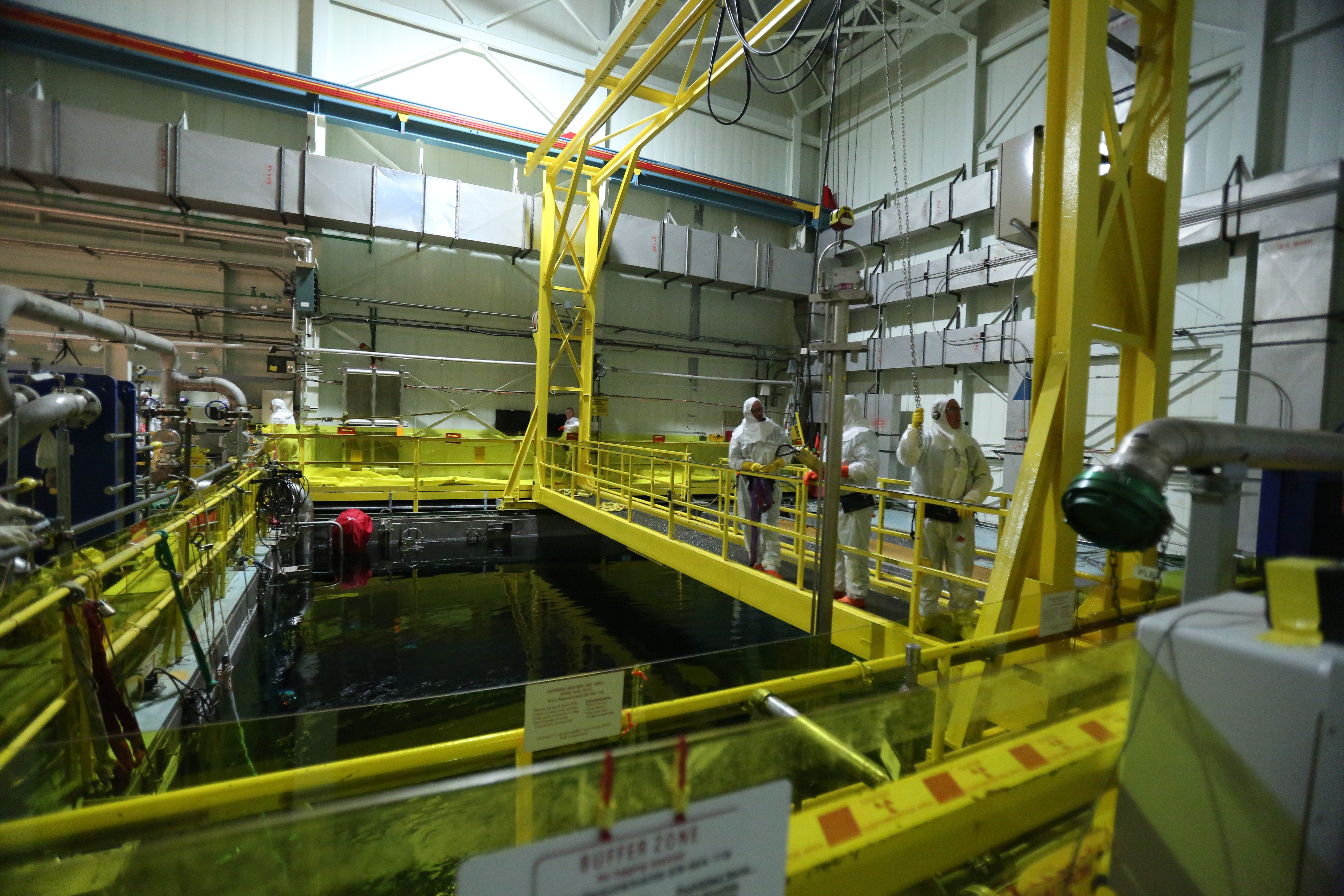 Workers remove a piece of equipment in the spent fuel pool of Unit 3, at the Indian Point Energy Center in Buchanan, Aug. 11, 2015.