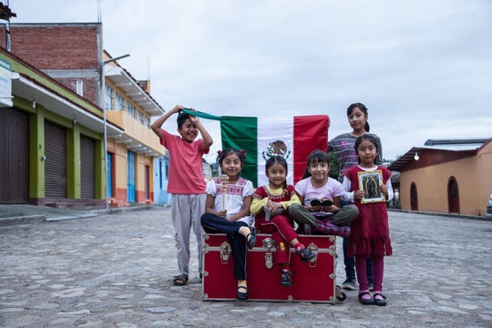 Children in Oaxaca, Mexico pose with a trunk from the Red Trunk Project.