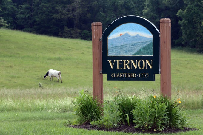 A Vernon welcome sign is pictured as a cow grazes in the field in Vernon, Vermont, June 19, 2017.