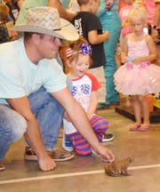 A Bowie, Texas, girl encourages her frog during a Jim Bowie Days race in this file photo. Similar events pack the schedule for this year's celebration, which includes a parade and rodeo, runs June 23-29.