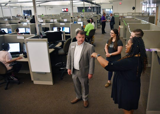 Zantea Townsend and William Overstreet, operations managers for The Results Companies, gives a tour of the call center formerly known as USA800. The center employs about 600 people locally.