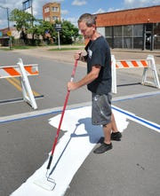 Wichita Falls artist David Fowler works to paint a musically themed guitar and piano crosswalk at the 7th at Ohio Street intersection in Downtown Wichita Falls Friday afternoon.