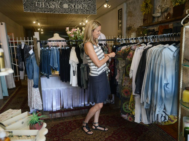 Sally Ritz, who owns the Towne House 2nd Fl at 524 Main St. in Zanesville, browses through the variety of clothing items available at her boutique.