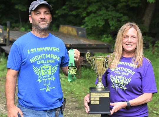 Lee and Lisa Emerson run and operate the Nightmare Challenge 5K Mud Run. They show off the medal and Corporate Cup for the event, which is held on July 13.
