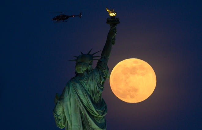 A helicopter flies past as the full moon rises behind the Statue of Liberty on May 18, 2019 in New York City.