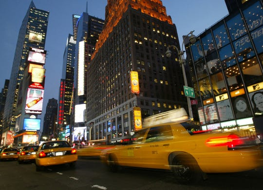 Taxicabs speed down Broadway near the intersection of Seventh Avenue and 42nd street in Times Square, in this 2005 file photo.