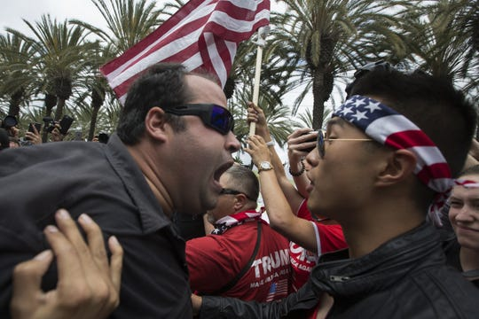 An anti-Trump protester and a Trump supporter clash outside a Donald Trump campaign rally at the Anaheim Convention Center on May 25, 2016 in Anaheim, California.