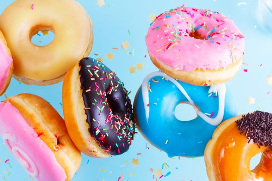 flying doughnuts scene - mix of multicolored sweet donuts with sprinkles on blue background close up