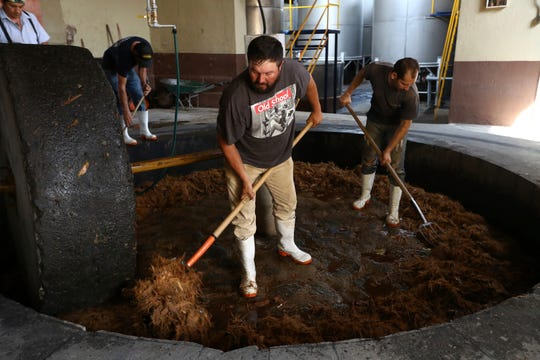 In this Wednesday, June 5, 2019 photo, workers use pitchforks to turn over agave, mashed by a giant lava stone, or tahona, in El Arenal, Jalisco state, Mexico.
