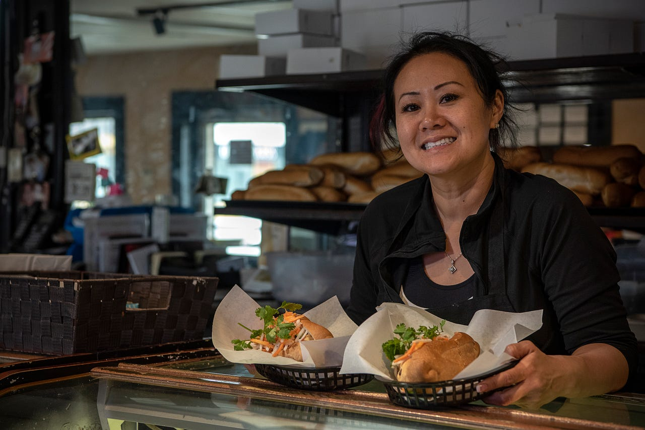 "Sue Nguyen, owner of Le Bakery in Biloxi, presents two of the eatery's banh mi sandwiches. Nguyen's parents established the popular bakery and sandwich shop after fleeing Vietnam in the 1970s. ""You can see the mayor here, or the construction worker,"" Nguyen says. ""I feel we've bridged the gap between different generations, economics and people."""