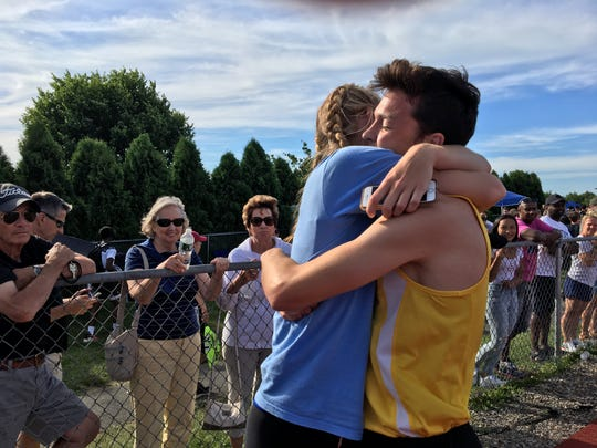 Point Boro's Devin Hart gets a hug from Shore Regional runner Hannah Birdsall after he wins the 3200 at the Meet of Champions.