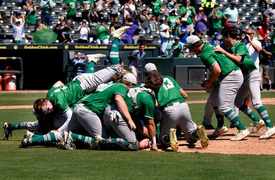 Centerfielder Colton Diebitsch slides over the top of the dog pile as Wall celebrates their UIL Class 3A state championship win over Blanco Saturday June 8, 2019. Final score was 2-1.