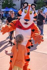 Tony the Tiger greets a young girl during the 2019 National Cereal Festival in downtown Battle Creek on Saturday, June 8, 2019.