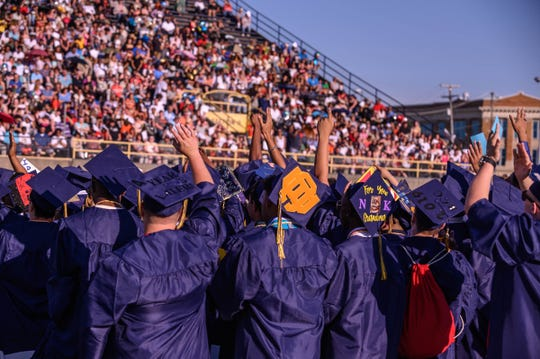 Students wave to the crowd at C.W. Post Field on Friday during the Battle Creek Central 2019 Graduation Ceremony.