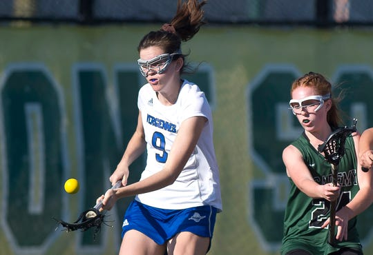 Vergennes/Mount Abraham's Hannah Kelly, left, scoops up a round ball ahead of St. Johnsbury's Ellie Rice in the Division II high school girls lacrosse championship game at Virtue Field on Friday, June 7, 2019.