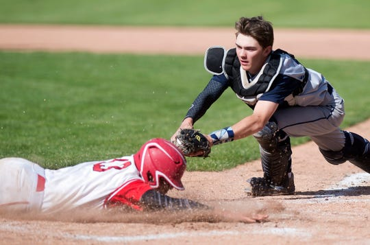 Mount Mansfield catcher Matt Wixson stretches to apply a tag to Champlain Valley's Jonah Roberts, who's safe for a run, in the Division I high school baseball state championship game at Centennial Field on Saturday, June 8, 2019.