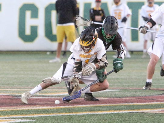 Harwood's Eamon Gilhuly and Stowe's Jake Ramos battle for the ball during a faceoff early in Stowe's 9-7 win to claim the 2019 D2 boys lacrosse title.