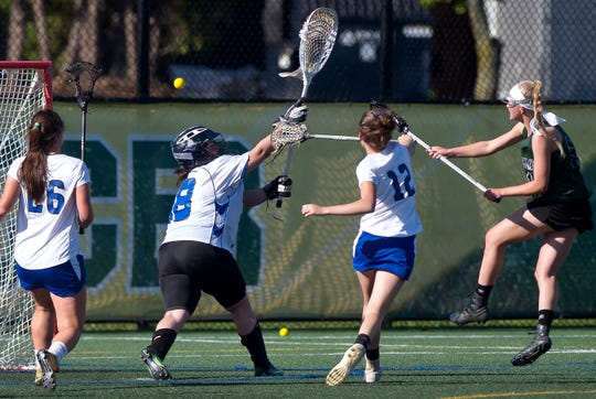 St. Johnsbury's Lilly Leach, right, fires a goal past  Vergennes/Mount Abraham goalie Ashley Tierney (18) in the Division II high school girls lacrosse championship game at Virtue Field on Friday, June 7, 2019.