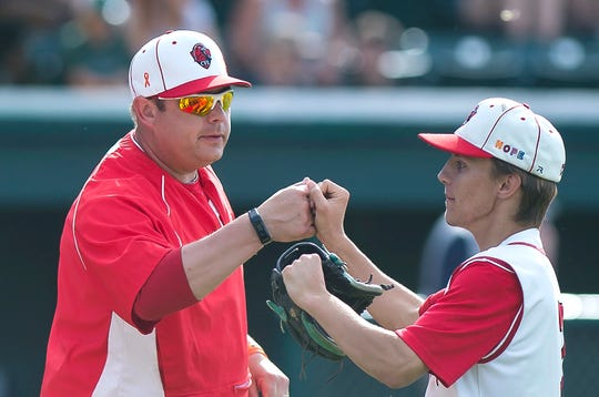 Champlain Valley coach Tim Albertson, left, bumps fists with Ryan Anderson between innings in the Division I high school baseball state championship game at Centennial Field on Saturday, June 8, 2019.