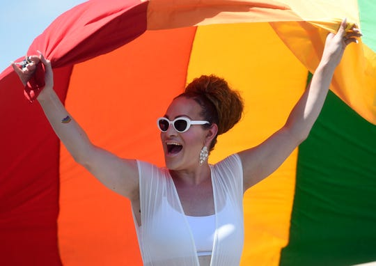 Anastasia Davis holds a rainbow flag while she marches in the Corpus Christi Pride parade, Saturday, June 8, 2019.