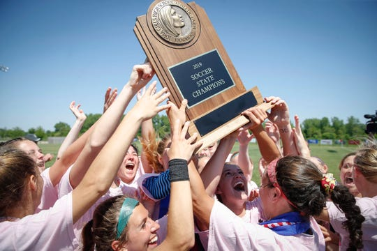 Members of the Davenport Assumption girls soccer team raise the Class 1A state championship trophy after a 1-0 win over North Polk during the 2019 Iowa high school girls state soccer tournament at Cownie Soccer Complex in Des Moines on Saturday, June 8, 2019.