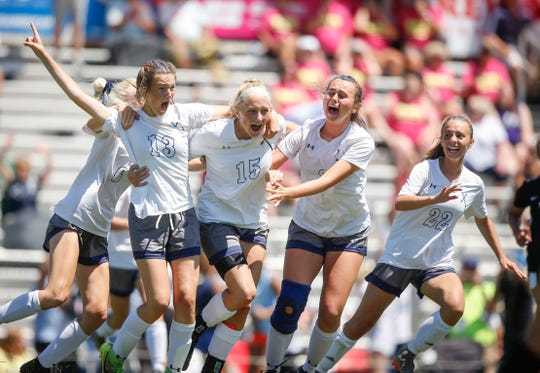 Members of the Cedar Rapids Xavier girls soccer team celebrate a Class 2A championship after scoring an overtime goal against Waverly-Shell Rock during the 2019 Iowa high school girls state soccer tournament at Cownie Soccer Complex in Des Moines on Saturday, June 8, 2019.