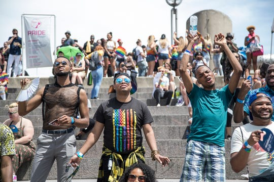 Festival goers include Emanuel Upshaw of Detroit, right, cheer as they enjoy the performance of Jharid at the Pride Stage during the Motor City Pride at Hart Plaza in Detroit, Saturday, June 8, 2019.