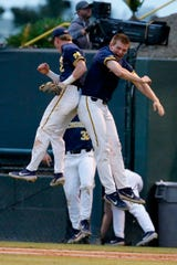 Michigan's Jack Blomgren, left, and Benjamin Keizer celebrate after UCLA was unable to score a run during the seventh inning of an NCAA tournament super regional game in Los Angeles, Friday, June 7, 2019. Michigan won, 3-2.